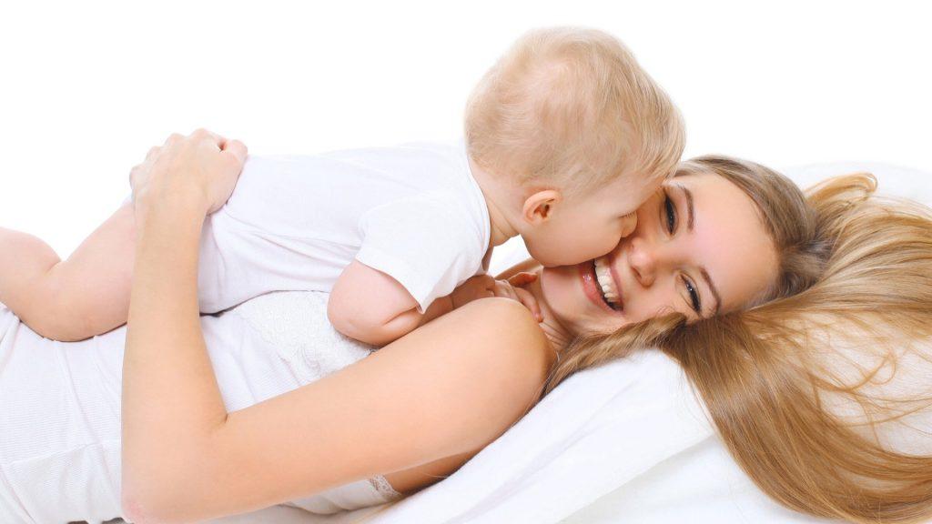 Mamma che fa tummy time con il proprio bambino neonato sulla pancia