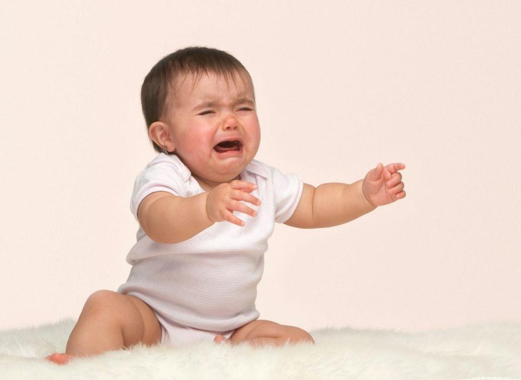 Bambino che non è capace di gattonare e rimane seduto, piangendo e richiamando l'attenzione dei propri genitori
